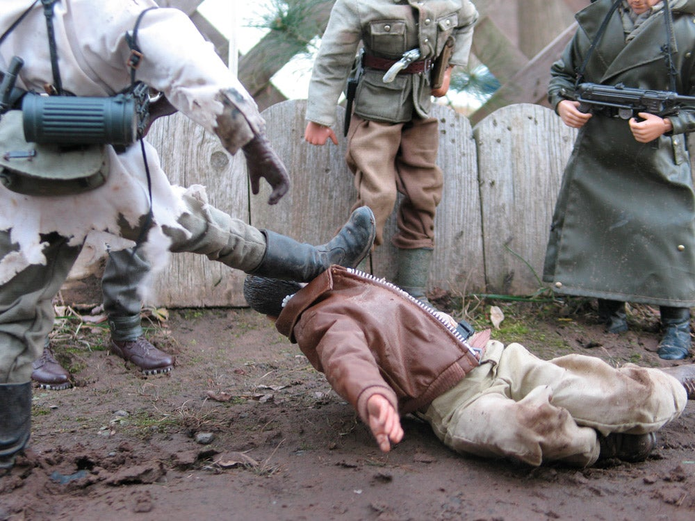 soldiers kicking man in the head