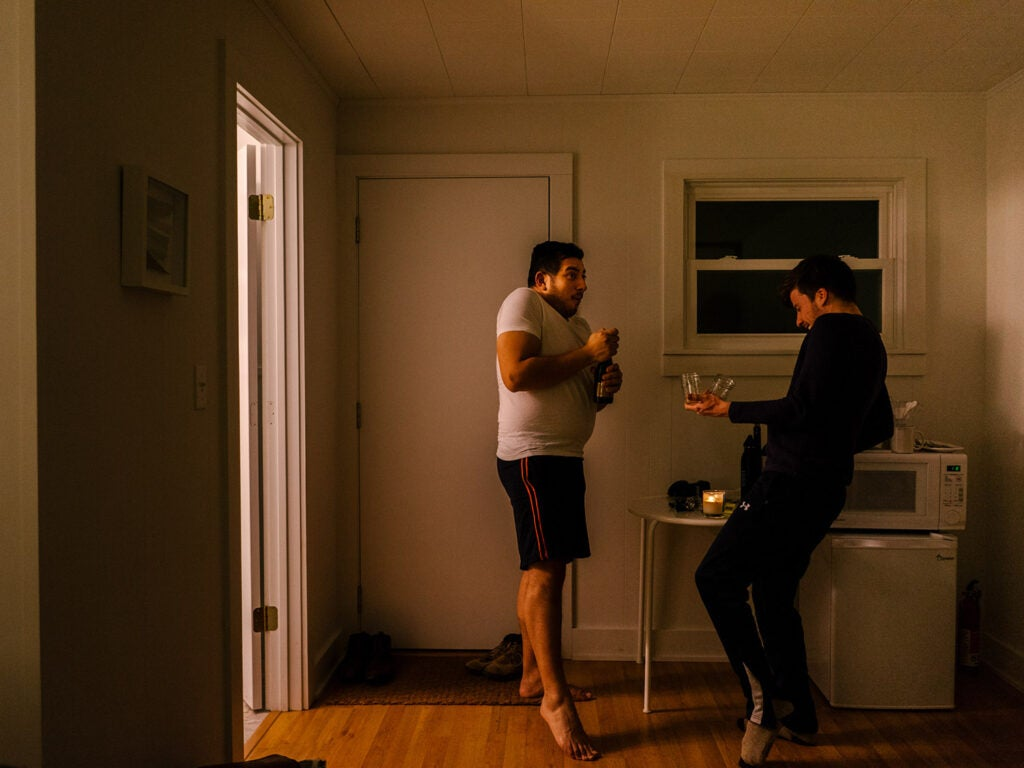 two men dancing with wine glasses