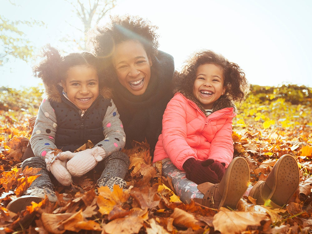 Portrait playful mother and daughters in autumn leaves in sunny park