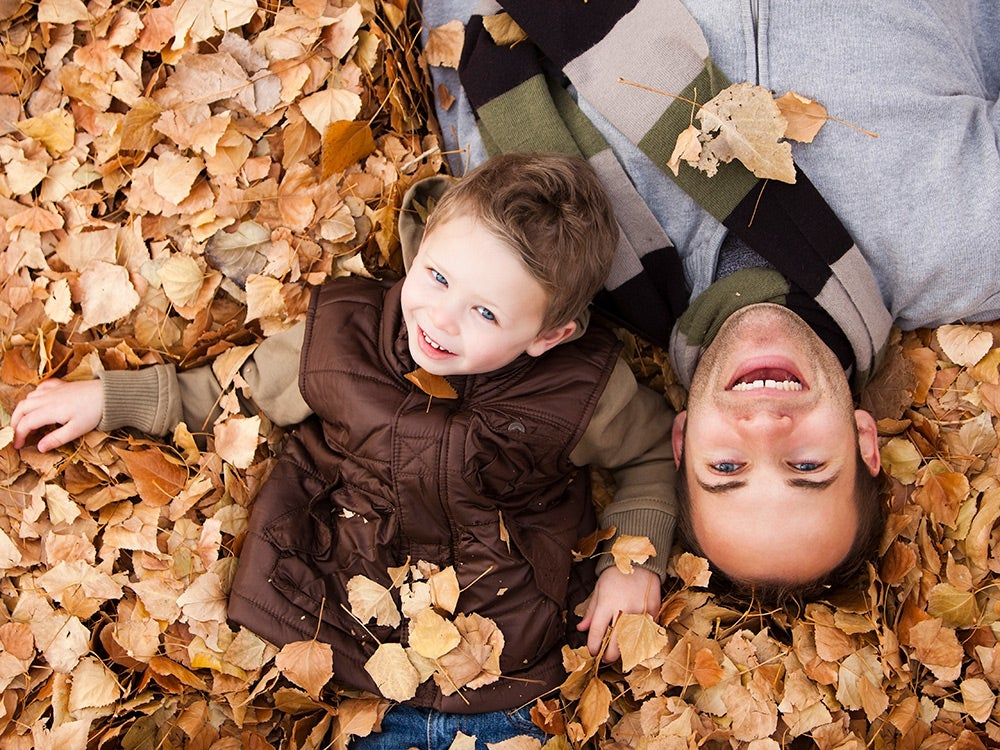 Father and son laying in autumn leaves