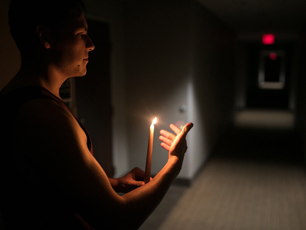 man holding a candle in dark room
