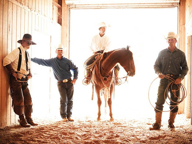 cowboys posing in stable with horse