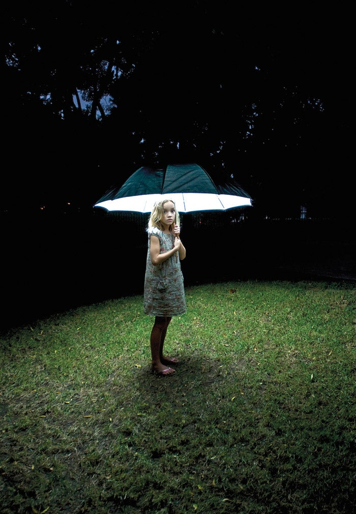 little girl with a lit umbrella at nigh