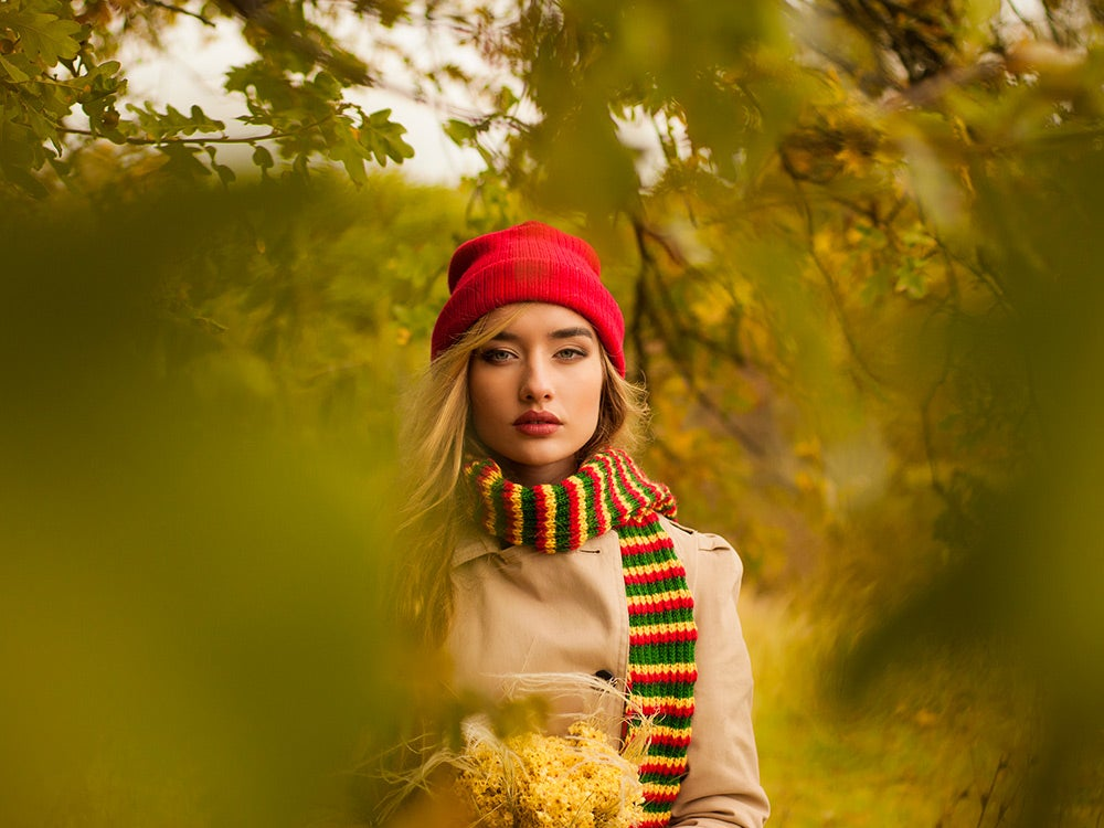 A woman wearing a knit hat and scarf in autumn