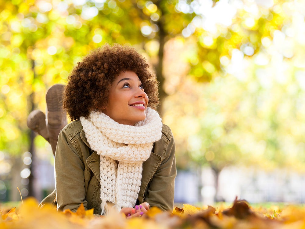 Young smiling woman lying on fall leaves