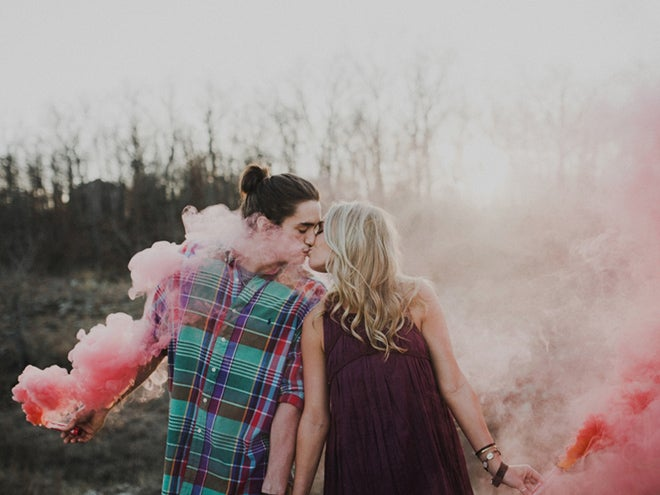 newly engaged couple kissing in smoke