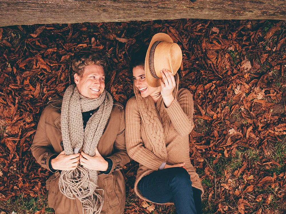 Young couple lying side by side on autumn leaves in a park
