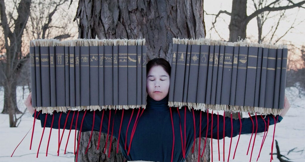 woman balancing many books on her arms