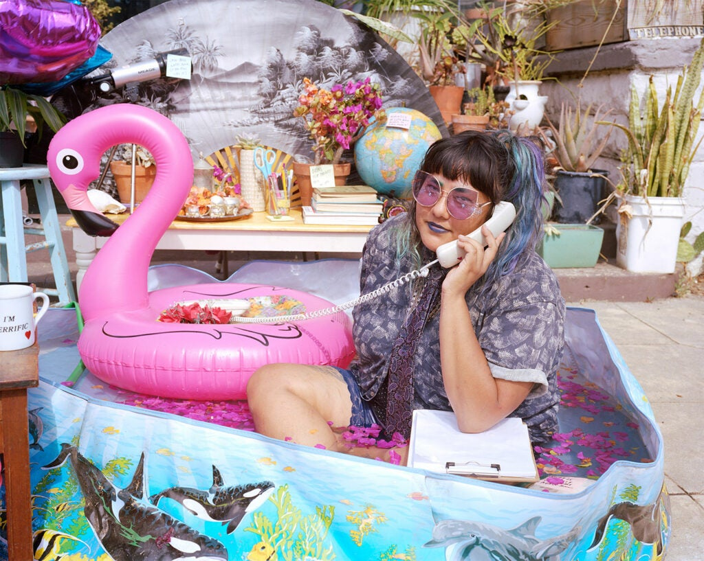 girl in a kiddy pool with a pink blow up flamingo
