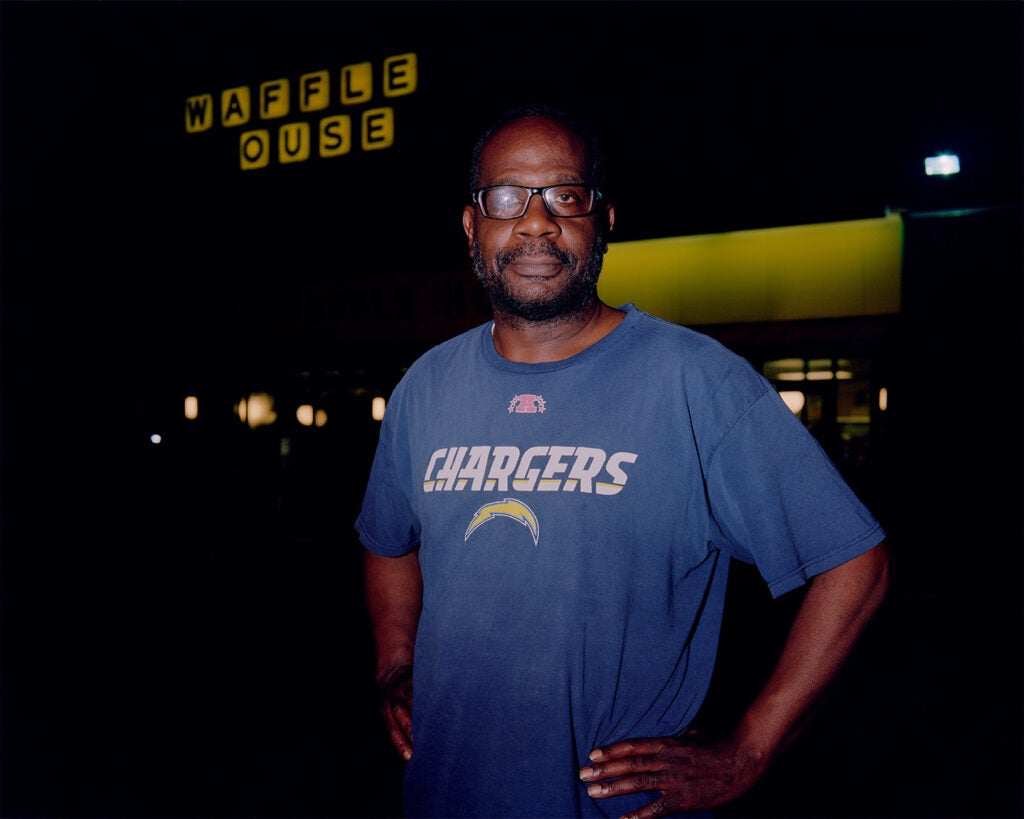 man outside waffle house in blue chargers shirt