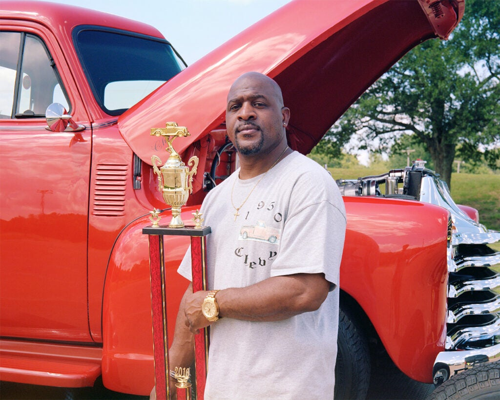 man with a trophy beside red vintage truck