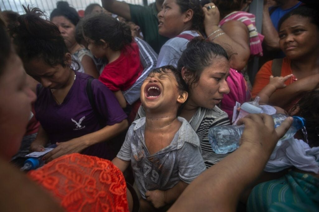 Migrant child screaming in a crowd