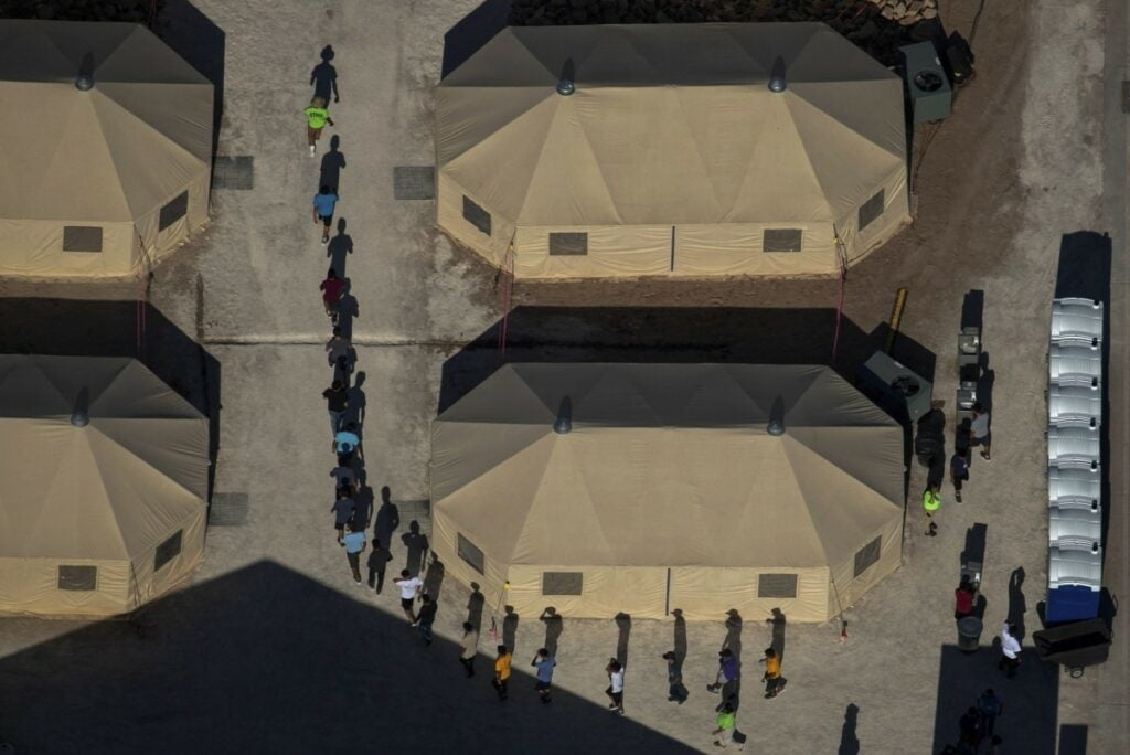 a line of migrants detained in a camp