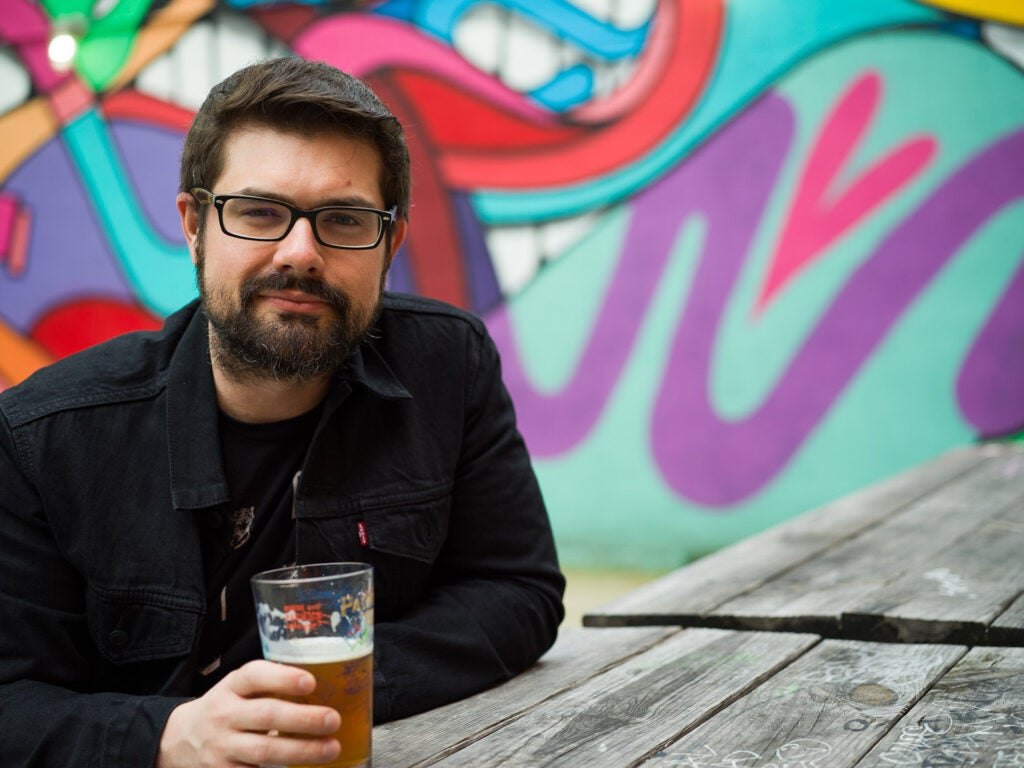 man with beer in front of graffiti