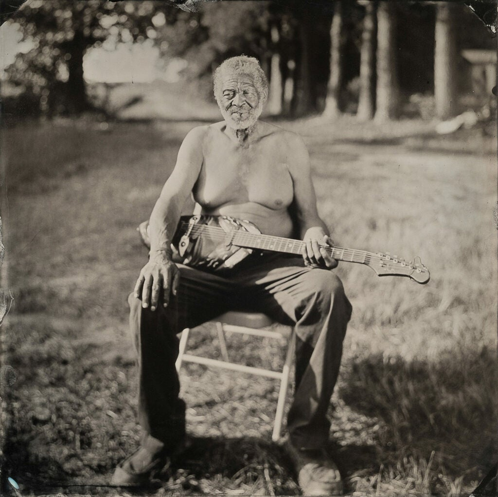 Freeman Vines shirtless with instrument in a field