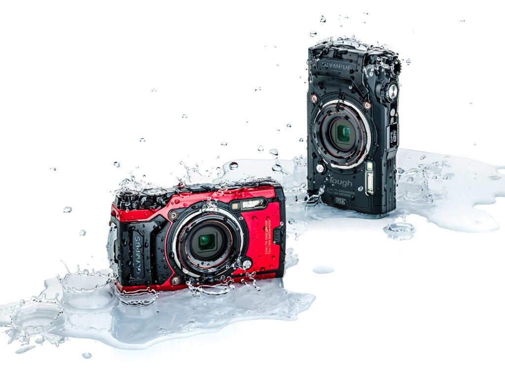 red and black olympus splashed with water