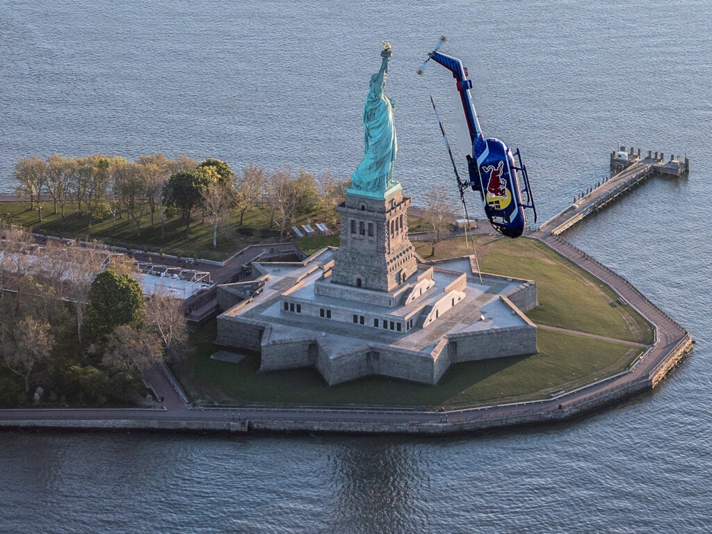 Red Bull Helicopter mid barrel roll near the Statue of Liberty.