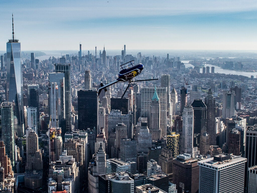 Aaron Fitzgerald in red bull helicopter inverted over the New York City skyline