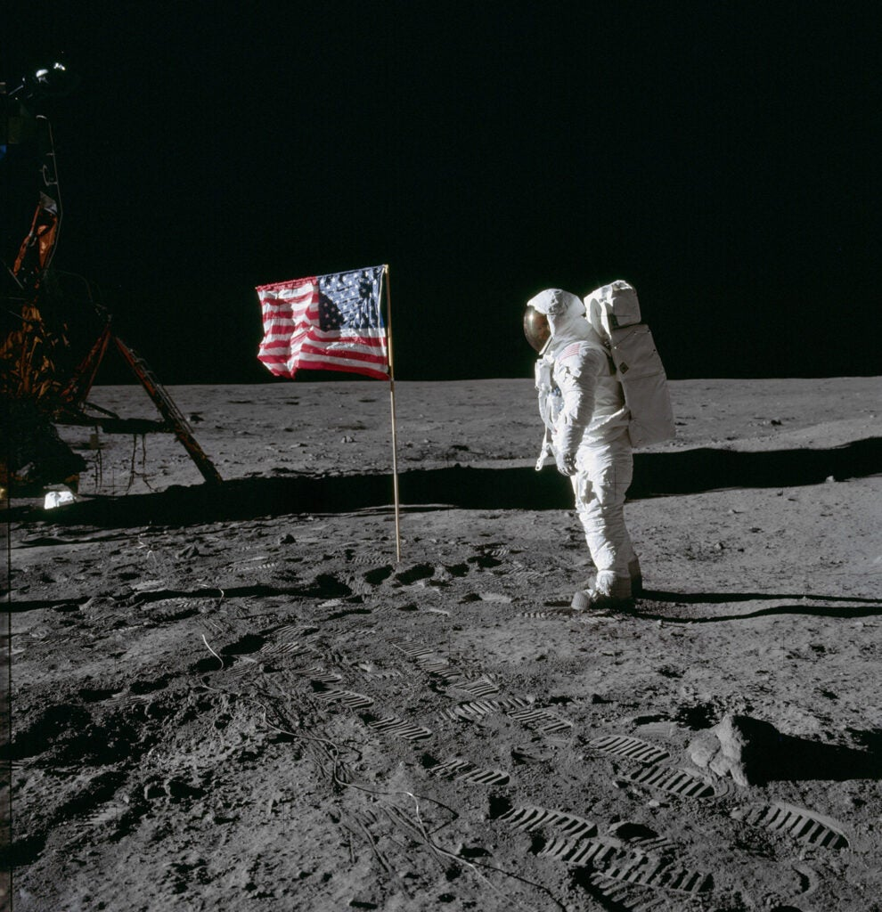 Astronaut Buzz Aldrin poses for photograph beside deployed U.S. flag