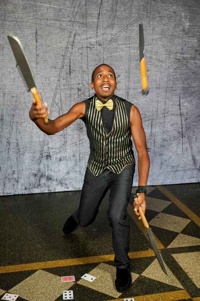 performer juggling knives in vest and bowtie