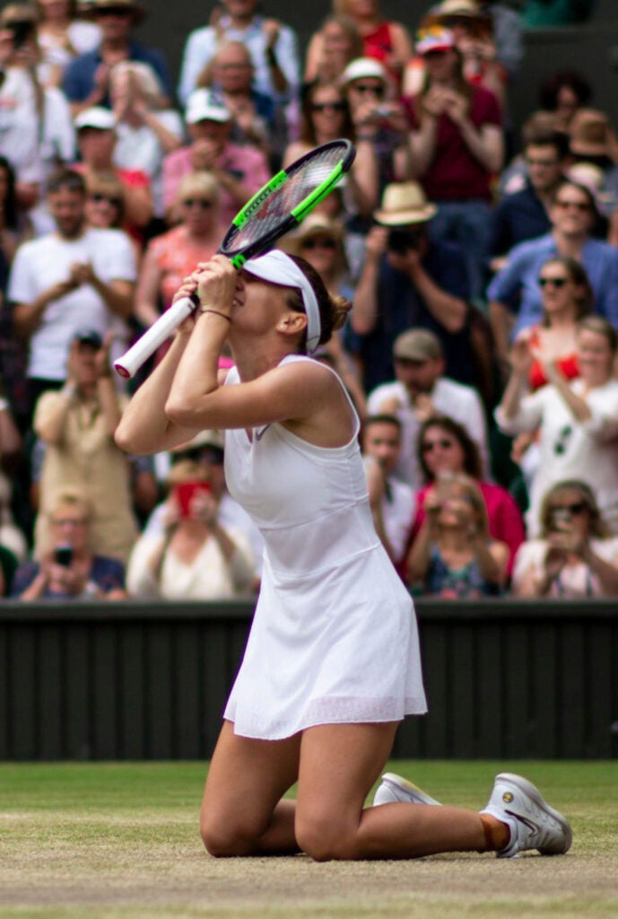 Tennis player kneeling with hands to face at Wimbledon Tennis Championships