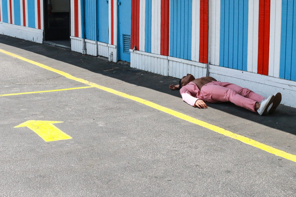 man in pink suit lying in the shade on the street