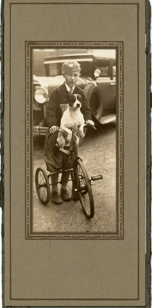 child and dog riding tricycle