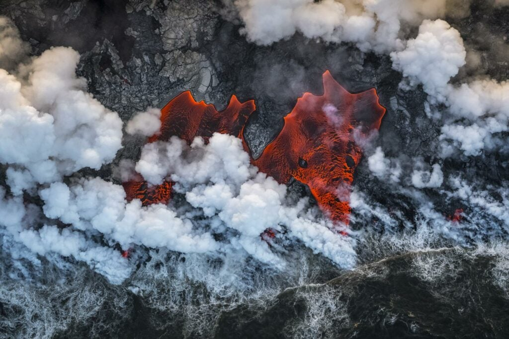 Aerial of lava flowing into the Pacific Ocean