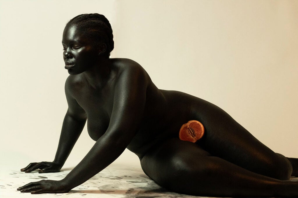 dark skinned woman hunched forward with painful expression