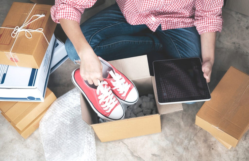 person surrounded by packages with ipad in hand putting shoes in box for shipment