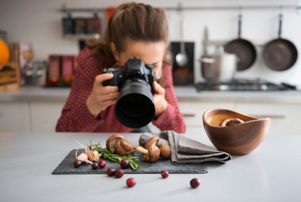 A photographer taking a close-up of food in a kitchen