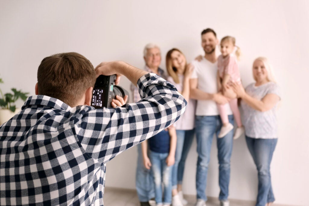 Professional photographer taking photo of family in studio