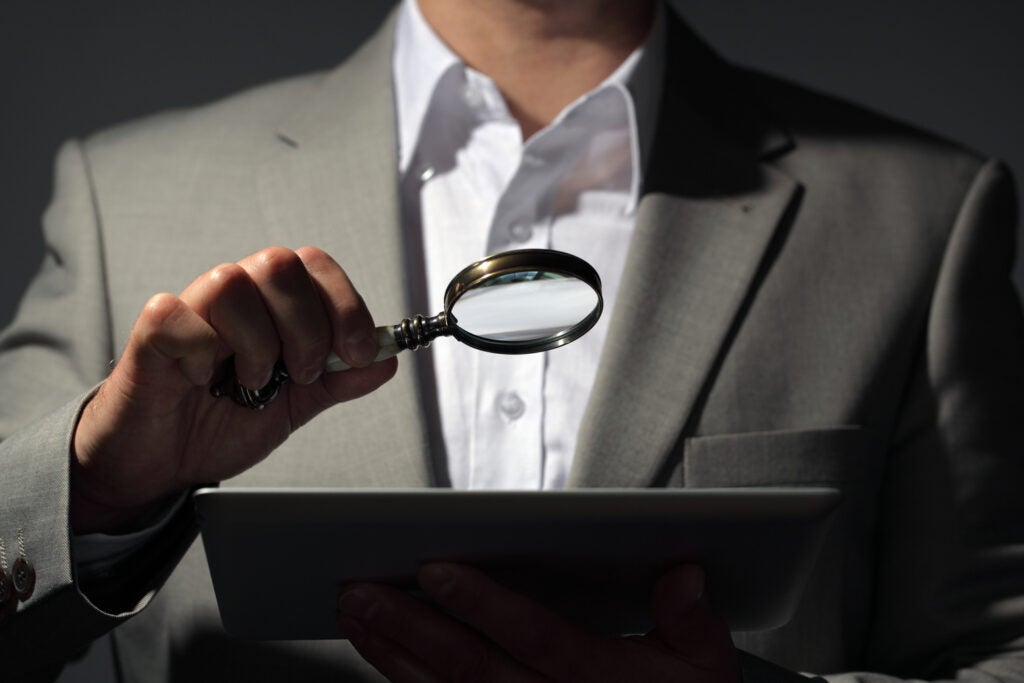 a man in a gray suit using a magnifying glass to look at a tablet