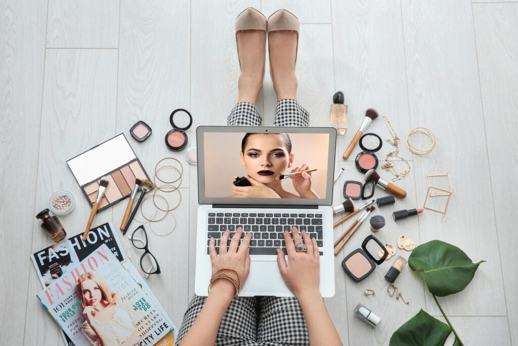 Person sitting on floor with laptop and watching online training for professional makeup artist