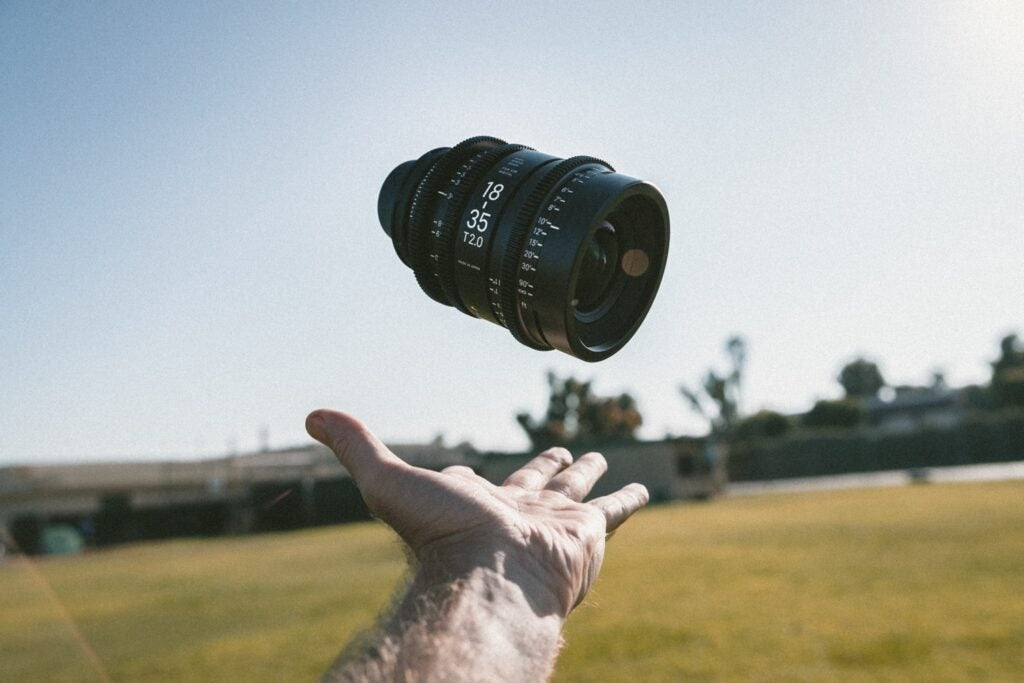 Hand throwing camera lens in the air