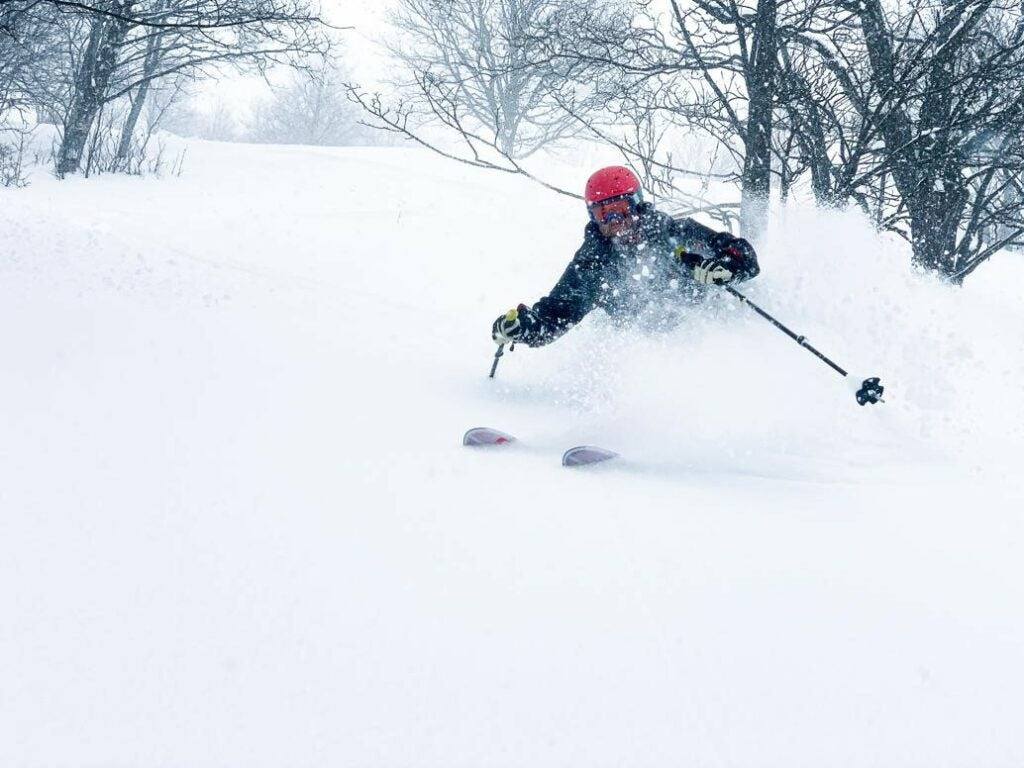 a less-aggressively compressed photo of a skiier skiing in snow while wearing a red hat during the winter
