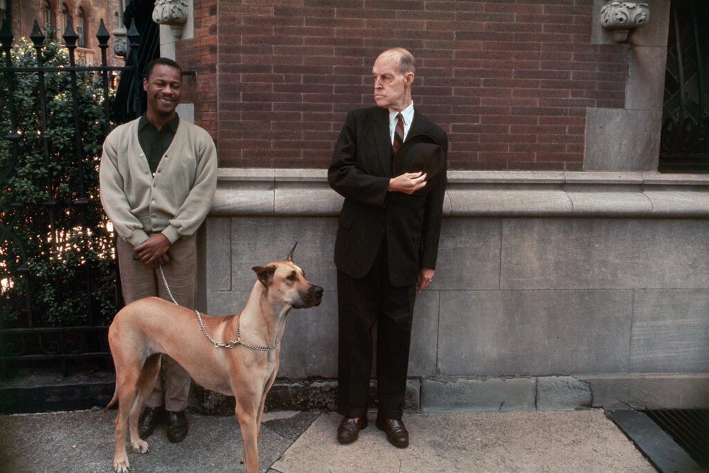 white man looking at black man with a big dog