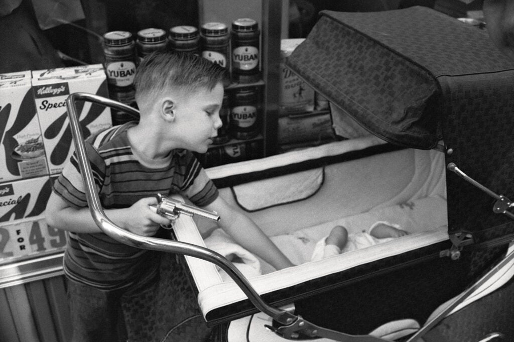 kid reaching into baby carriage